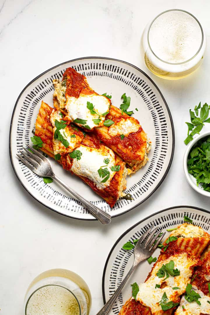 Two plates filled with baked three cheese manicotti