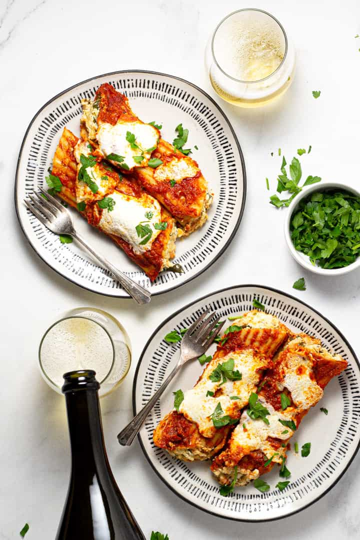 Two plates filled with baked three cheese manicotti garnished with fresh parsley