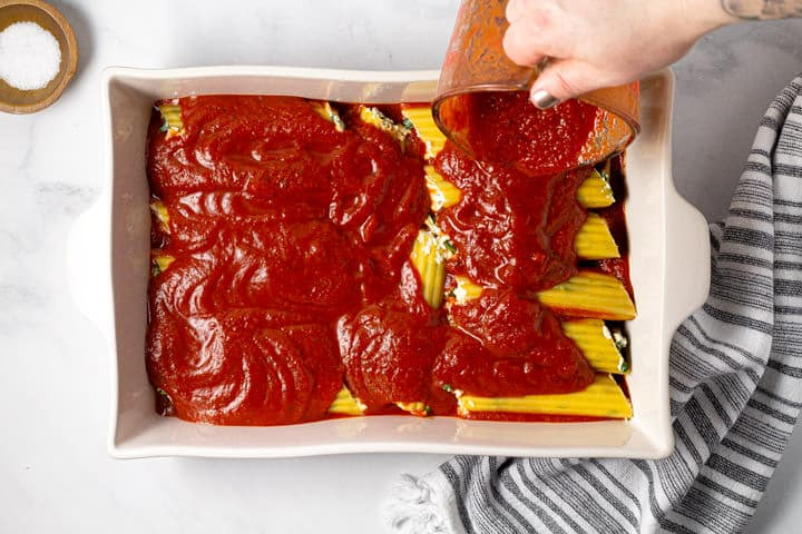 A hand pouring spaghetti sauce over a pan of filled manicotti noodles