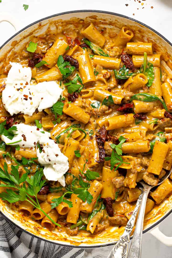 Overhead shot of a large white pot filled with one pot pasta garnished with fresh parsley