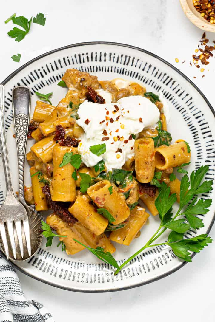 Black and white plate filled with sausage rigatoni garnished with fresh parsley