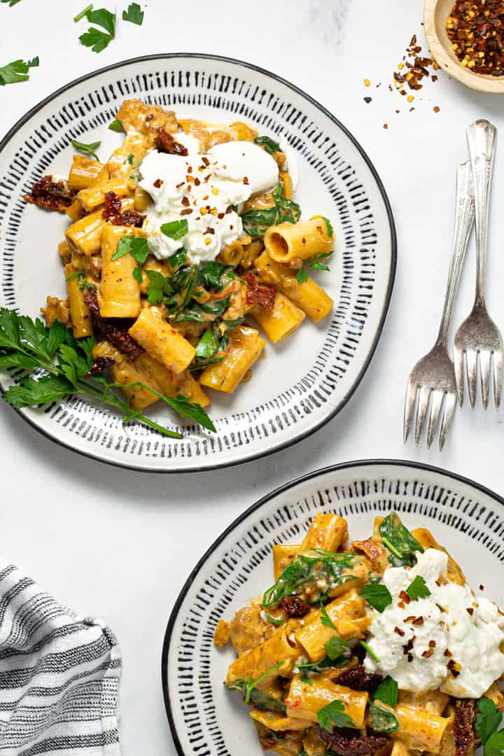 Two black and white plate filled with sausage rigatoni garnished with fresh parsley