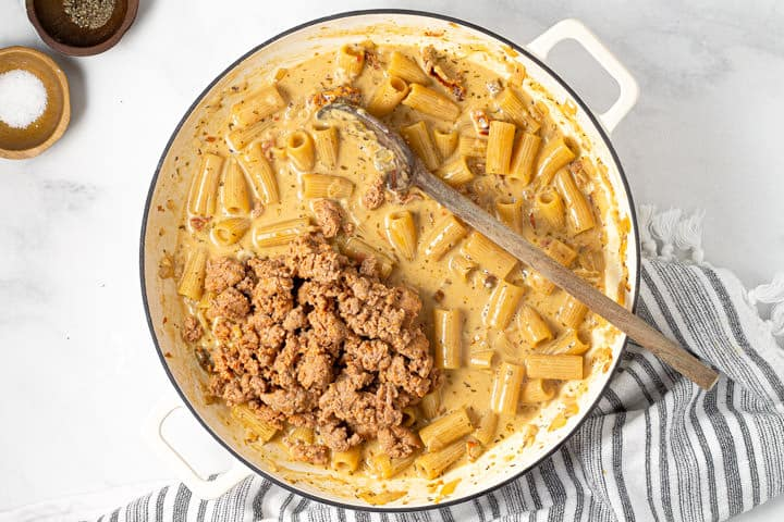 Browned sausage and cooked rigatoni in a large pot