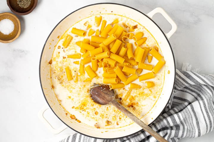 Uncooked rigatoni in a large white pan of broth and half and half