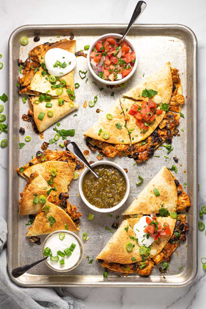 Overhead shot of  a sheet pan filled with quesadillas garnished with sliced green onion