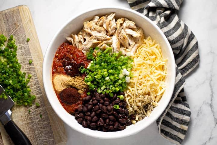Large white bowl filled with ingredients to make sheet pan quesadillas