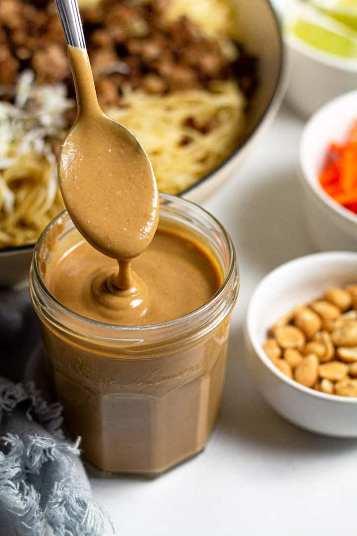 Creamy peanut sauce dripping off a spoon over a jar of the sauce