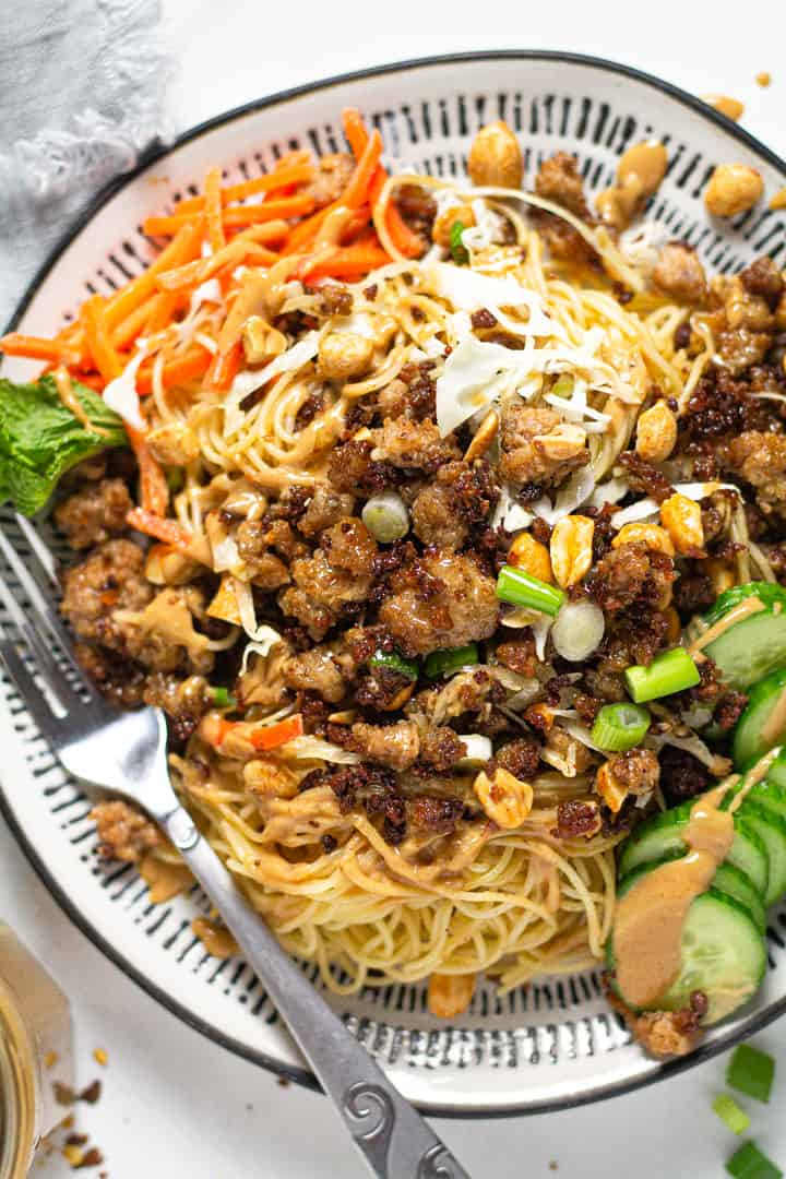 Overhead shot of a black and white plate with Thai pork noodles garnished with sliced green onions