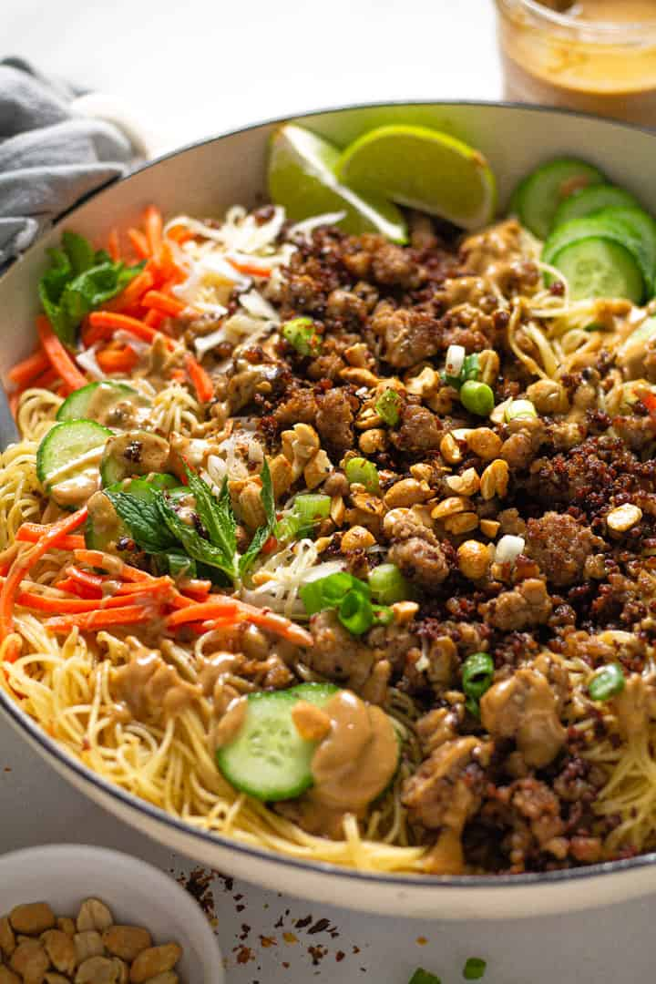 Close up shot of a large white pot filled with Thai pork noodles and fresh veggies