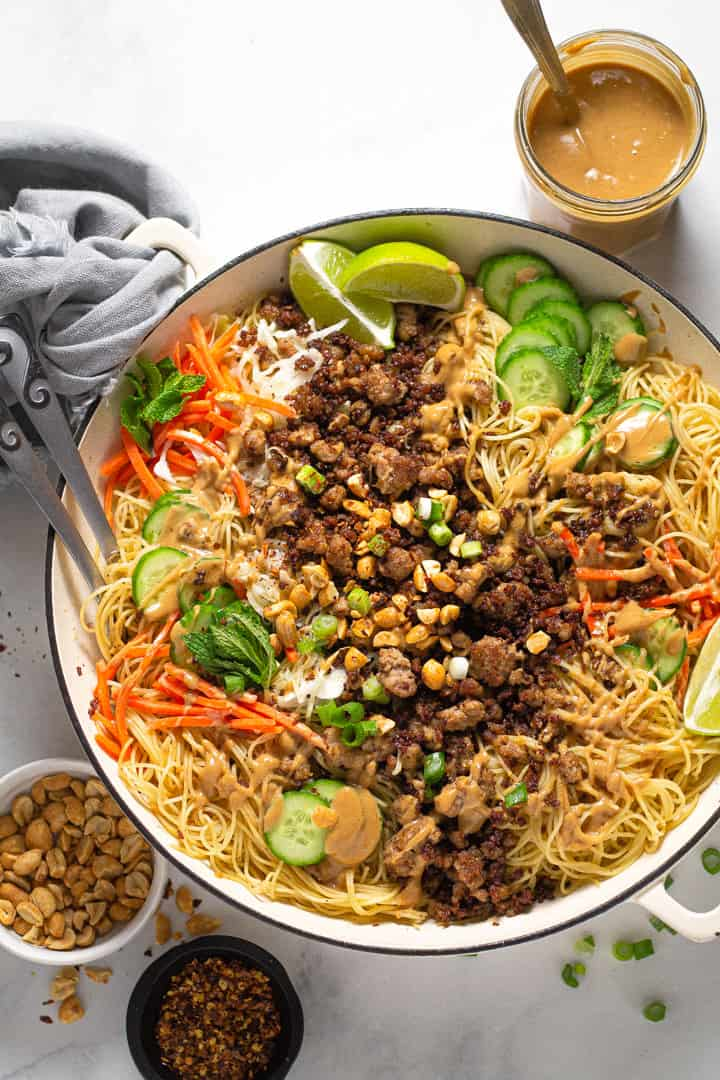 Overhead shot of a large white pot filled with Thai pork noodles and fresh veggies