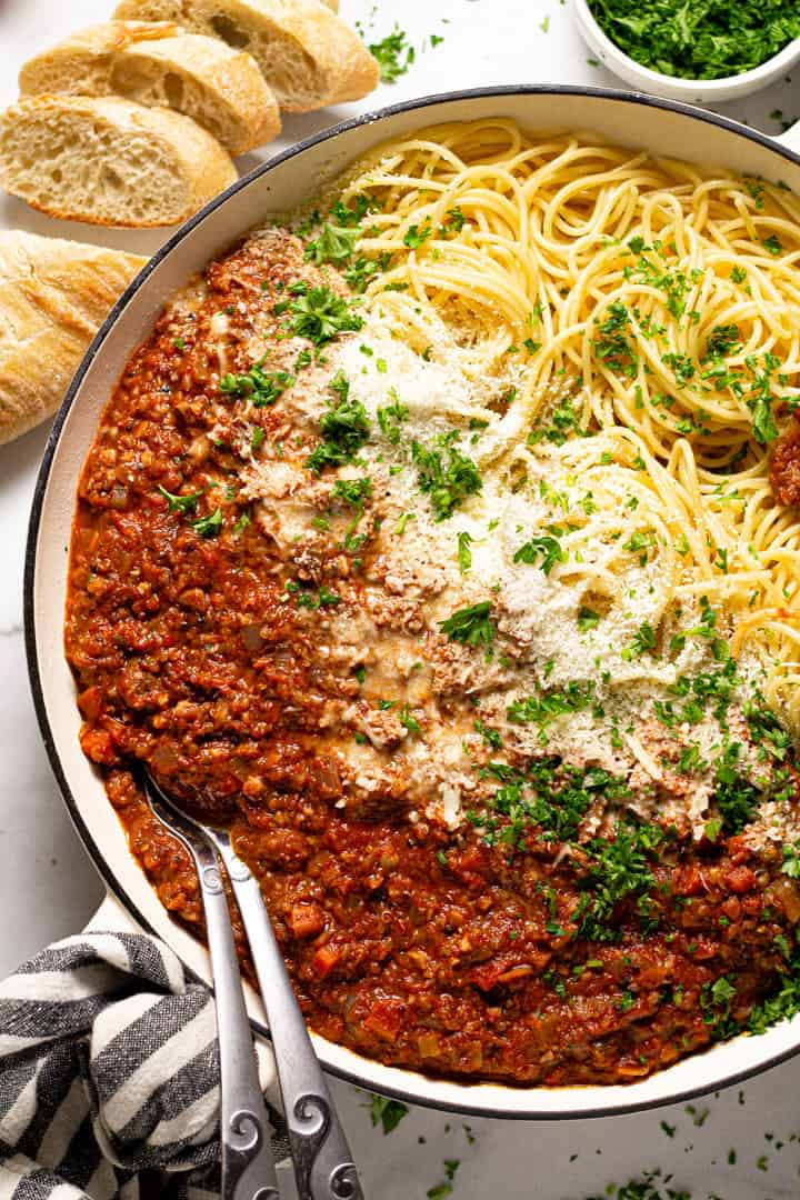 Overhead shot of a pan filled with spaghetti and vegetarian bolognese with fresh chopped parsley
