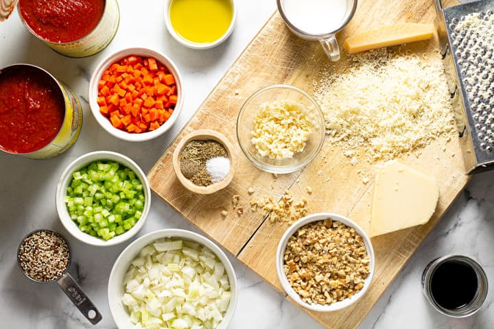 White marble counter top with ingredients to make vegetarian bolognese