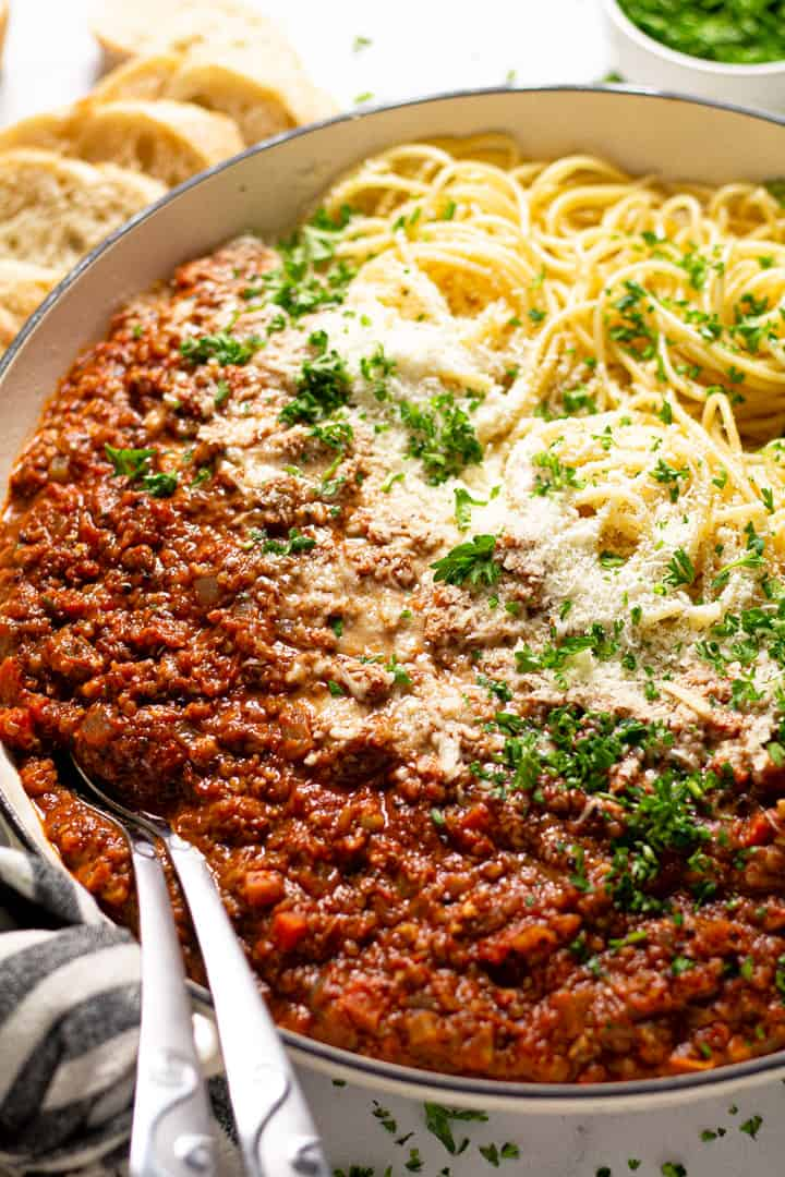 Close up shot of a pan filled with spaghetti and vegetarian bolognese with fresh chopped parsley