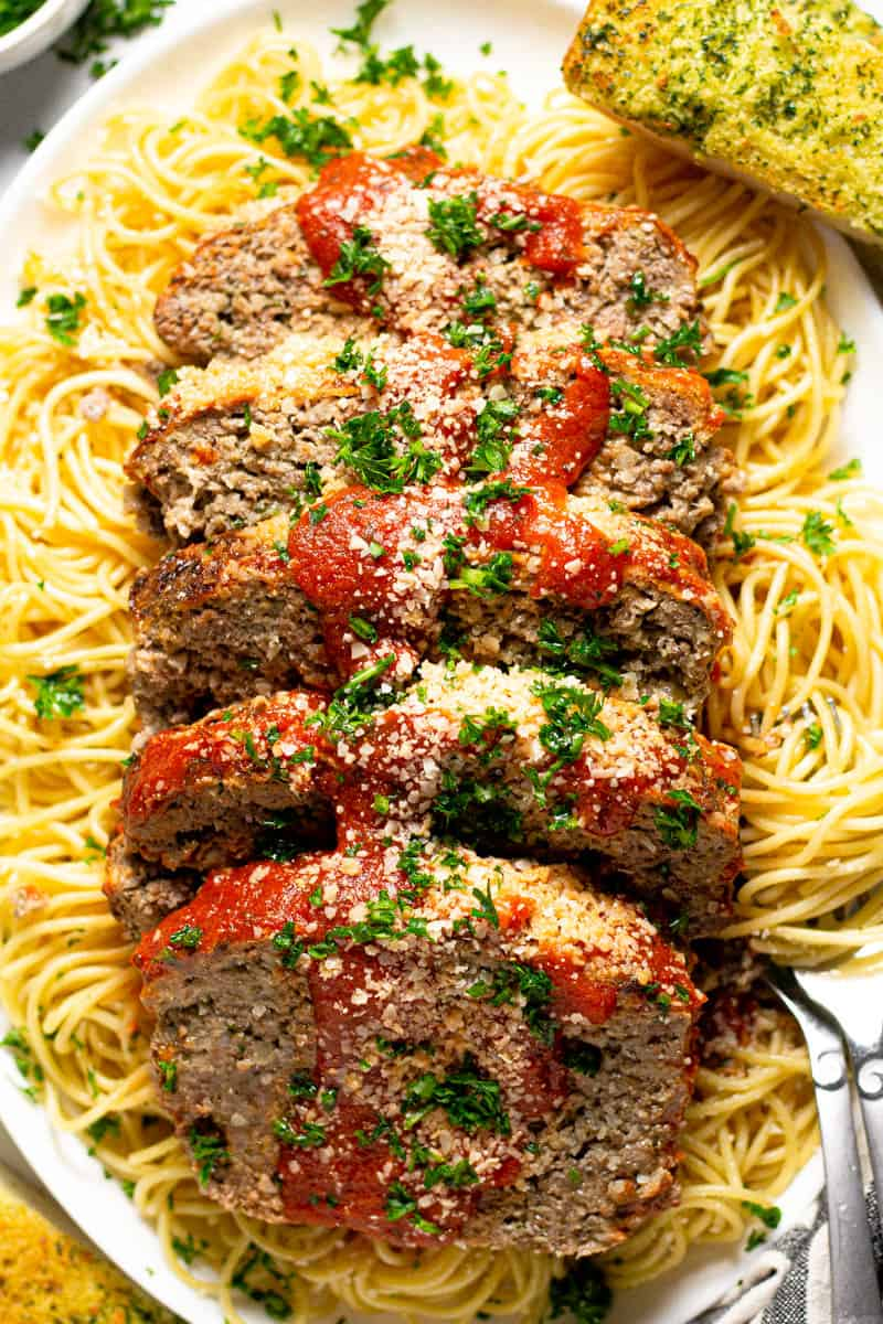 Large white platter with an Italian meatloaf sliced on top of a bed of spaghetti noodles