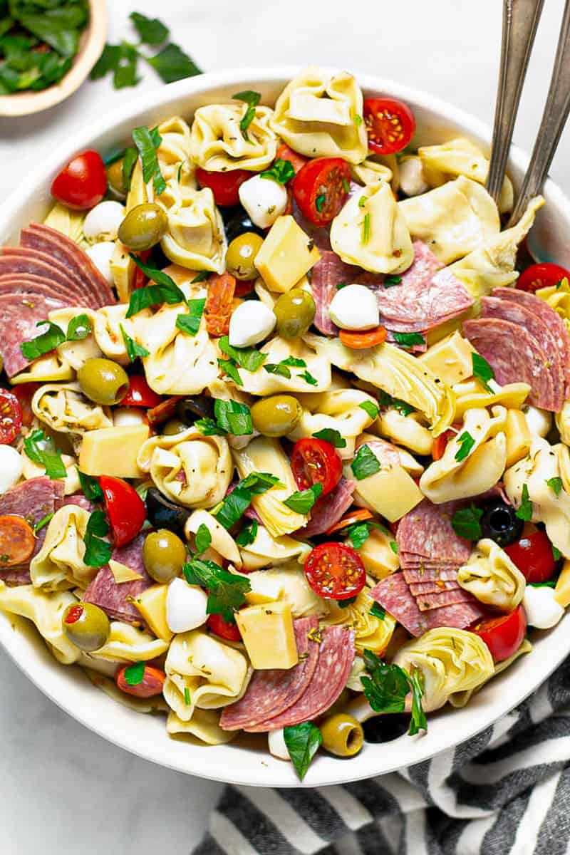 Overhead shot of a white bowl filled with pasta salad loaded with meat and veggies