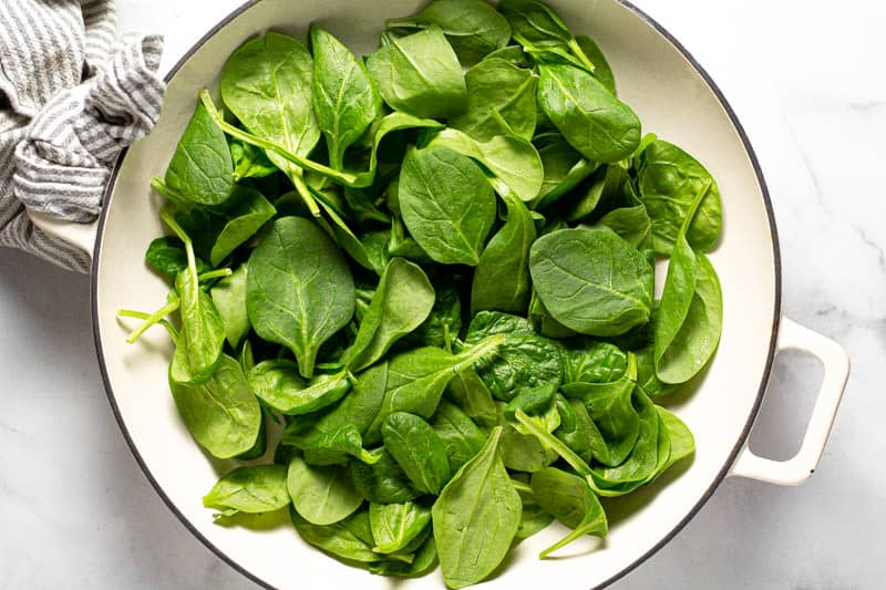Overhead shot of a baking dish filled with fresh spinach leaves