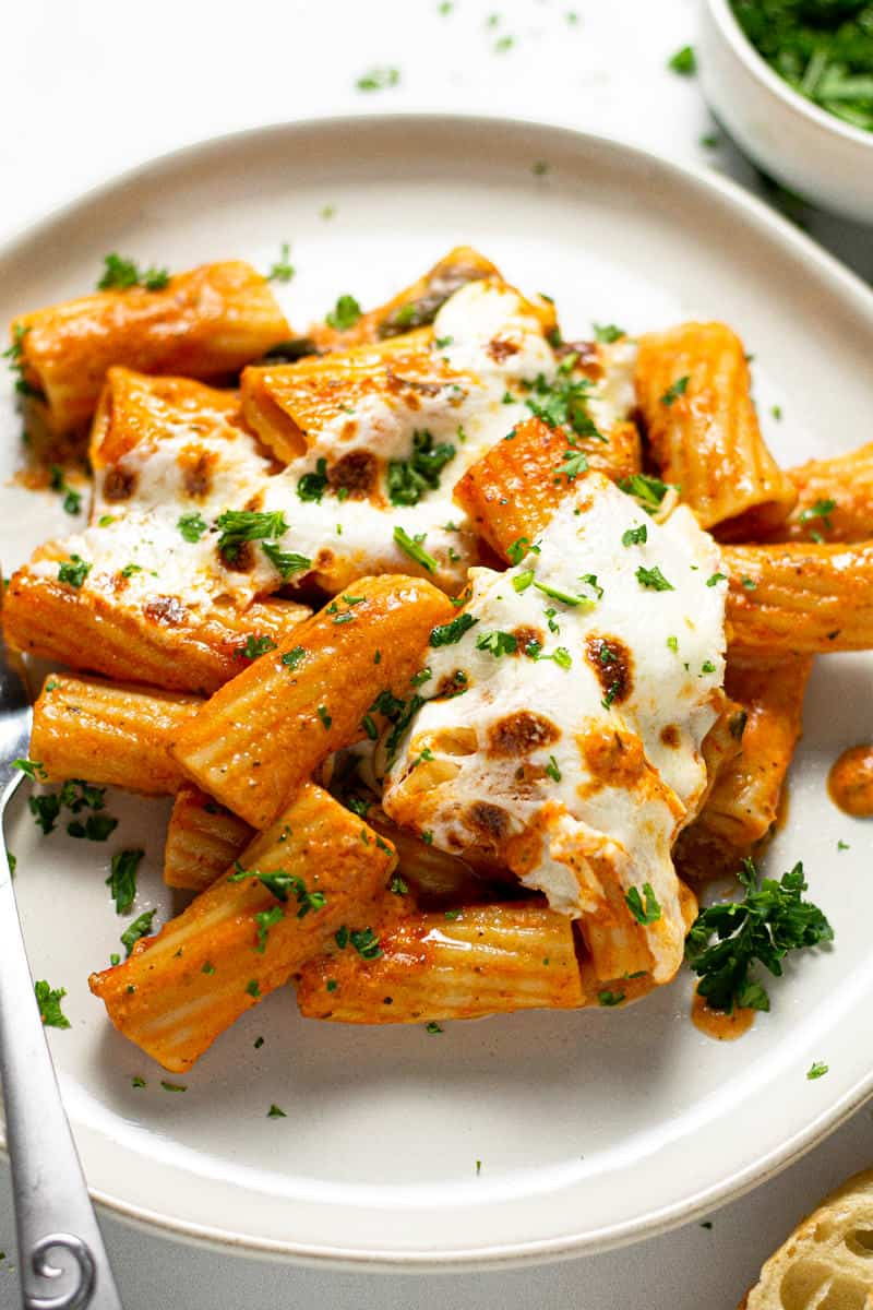 Close up shot of a plate of baked pasta garnished with fresh parsley