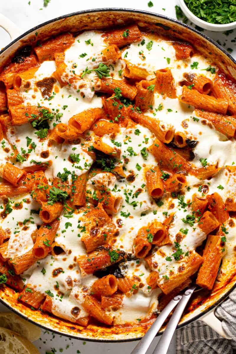 Overhead shot of a round baking dish filled with baked pasta garnished with fresh parsley