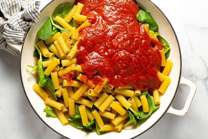 Overhead shot of a baking dish filled with fresh spinach leaves uncooked noodles and spaghetti sauce
