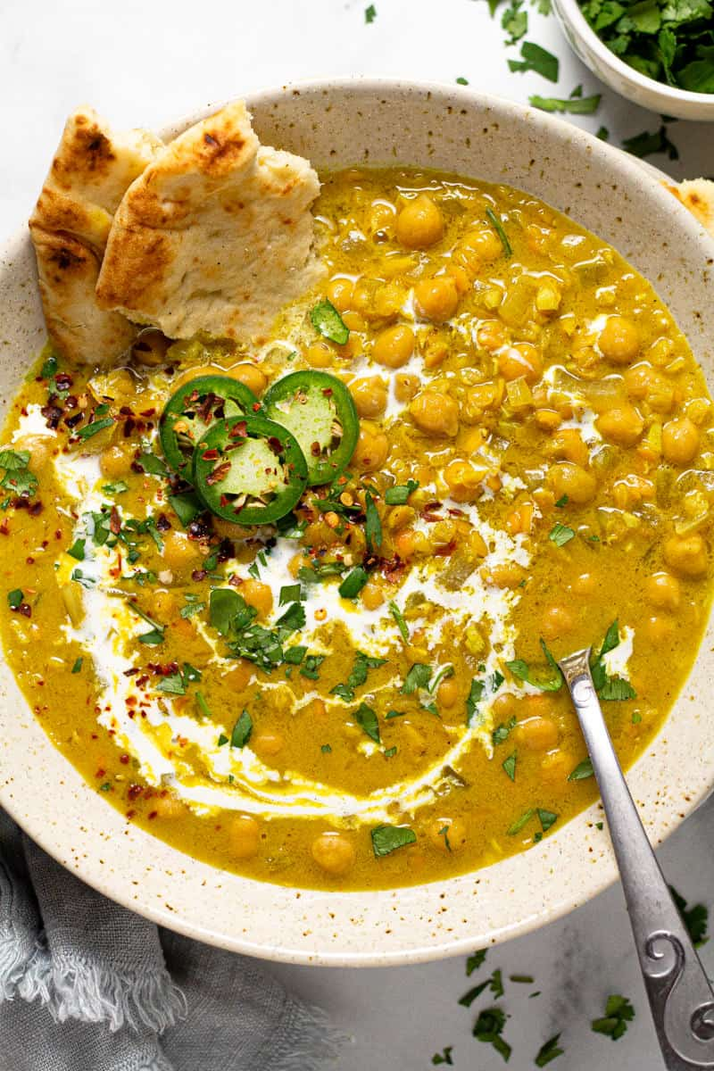 Overhead shot of a bowl of curry lentil soup garnished with coconut milk and cilantro