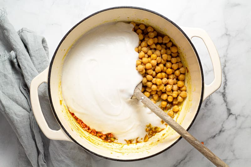 Large white pot filled with chickpeas red lentils and coconut milk