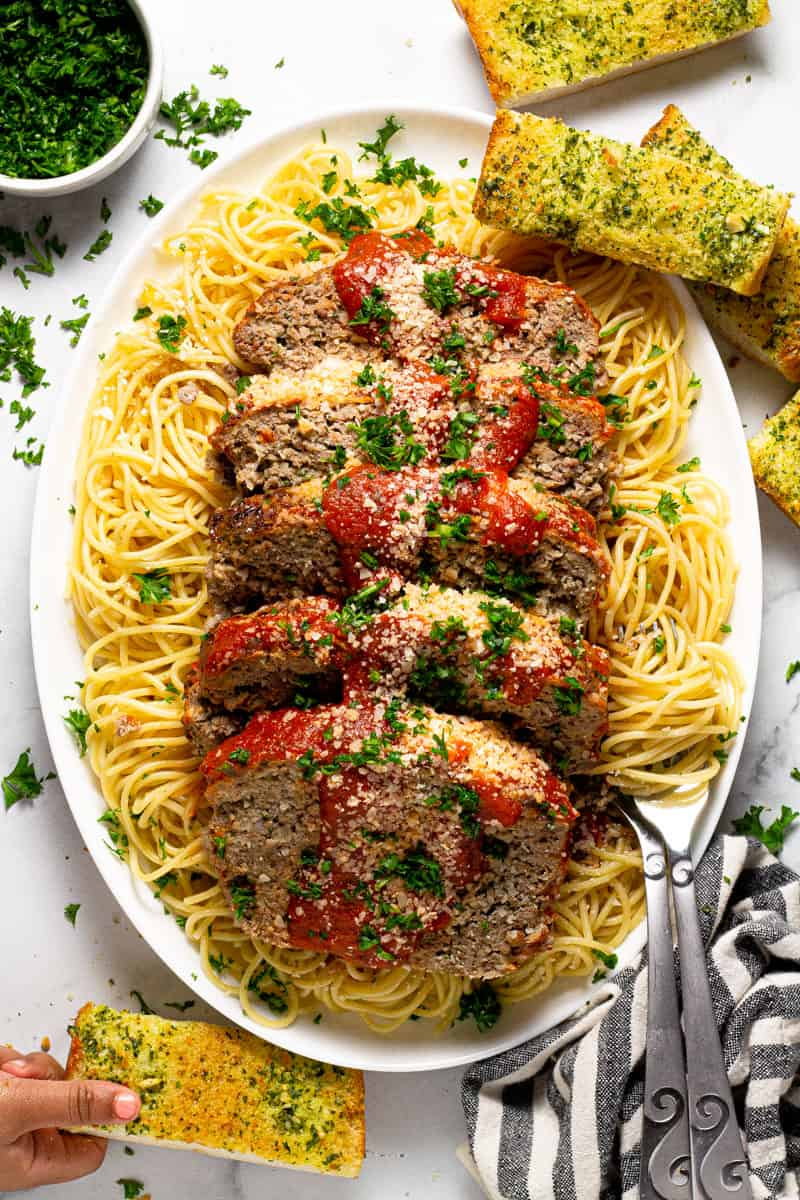 Overhead shot of a white platter filled with cooked spaghetti and sliced Italian meatloaf