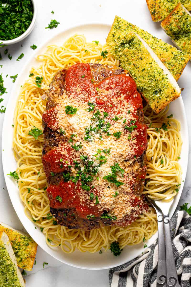 Overhead shot of a white platter filled with cooked spaghetti and Italian meatloaf