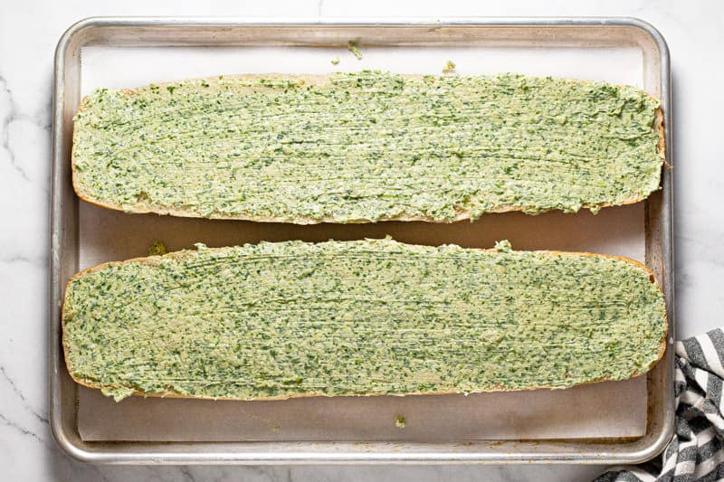 A large baking sheet with homemade garlic bread ready to be baked