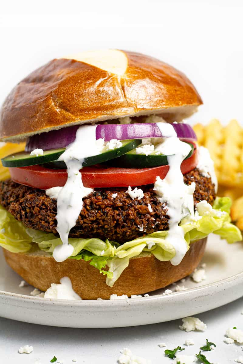 Close up shot of a vegan falafel burger straight on drizzled with yogurt dill sauce