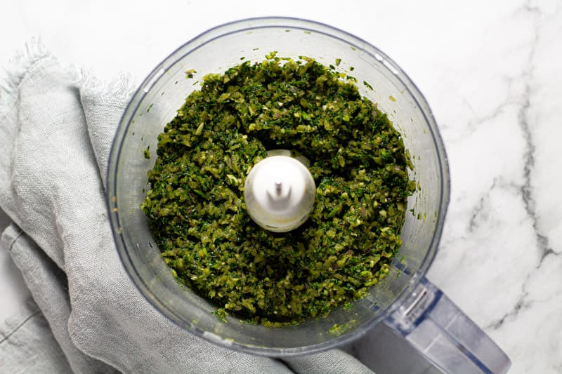 Food processor filled with minced herbs onion and garlic