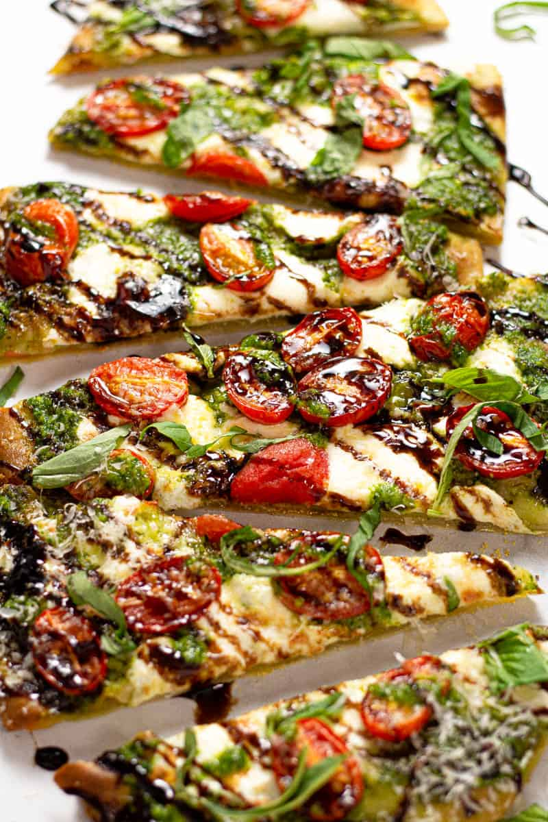 Close up shot of a Caprese flatbread pizza on a white marble counter top