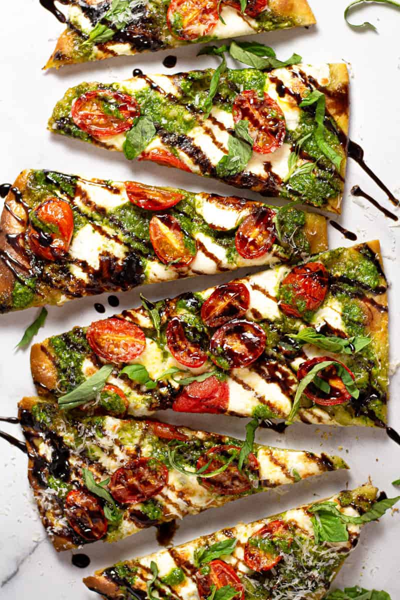 Overhead shot of a Caprese flatbread pizza on a white marble counter top