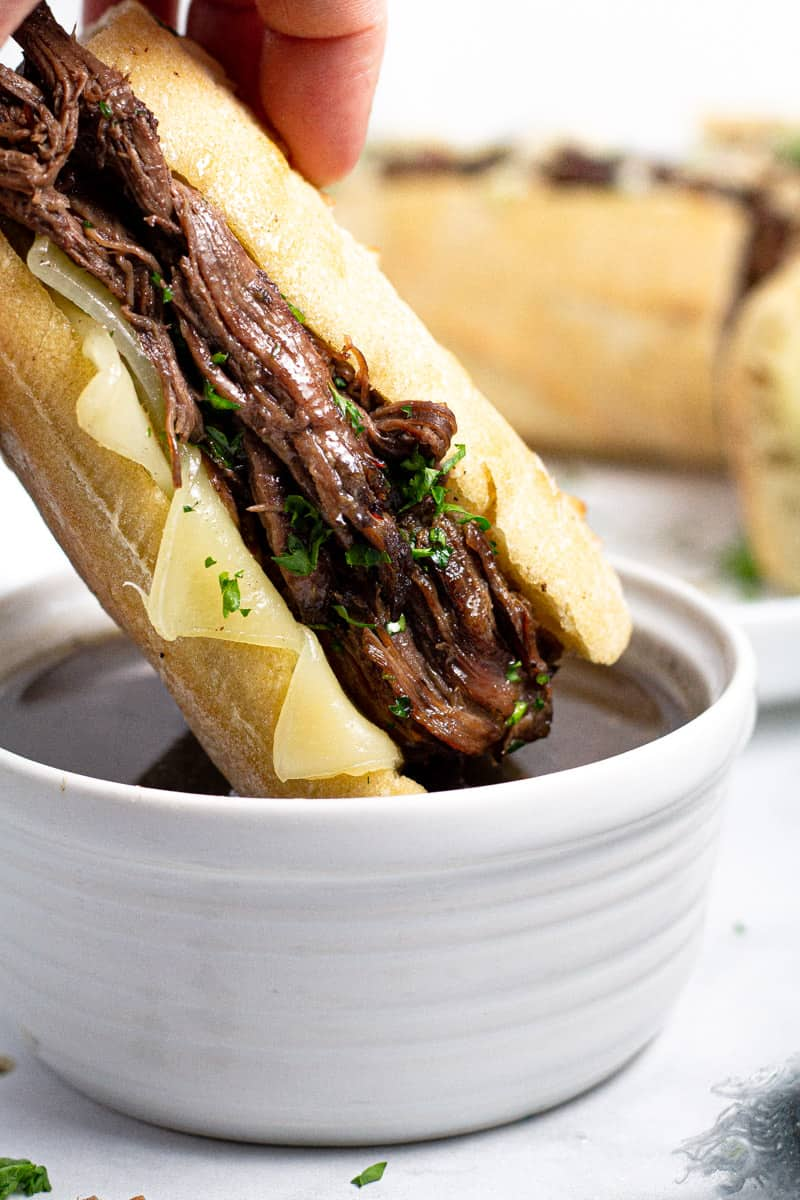 Close up shot of a French dip being dipped in au jus