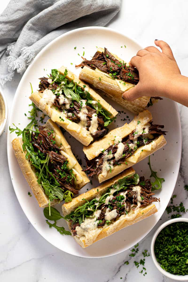 Large white platter filled with instant pot French dip sandwiches