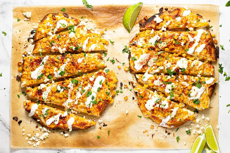 Overhead shot of two Mexican street corn flatbreads garnished with fresh chopped cilantro