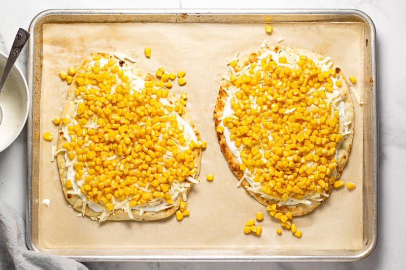 Large baking sheet with two Mexican street corn flatbreads with creamy sauce and corn on them