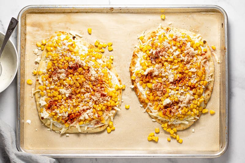 Large baking sheet with two Mexican street corn flatbreads ready to be baked in the oven