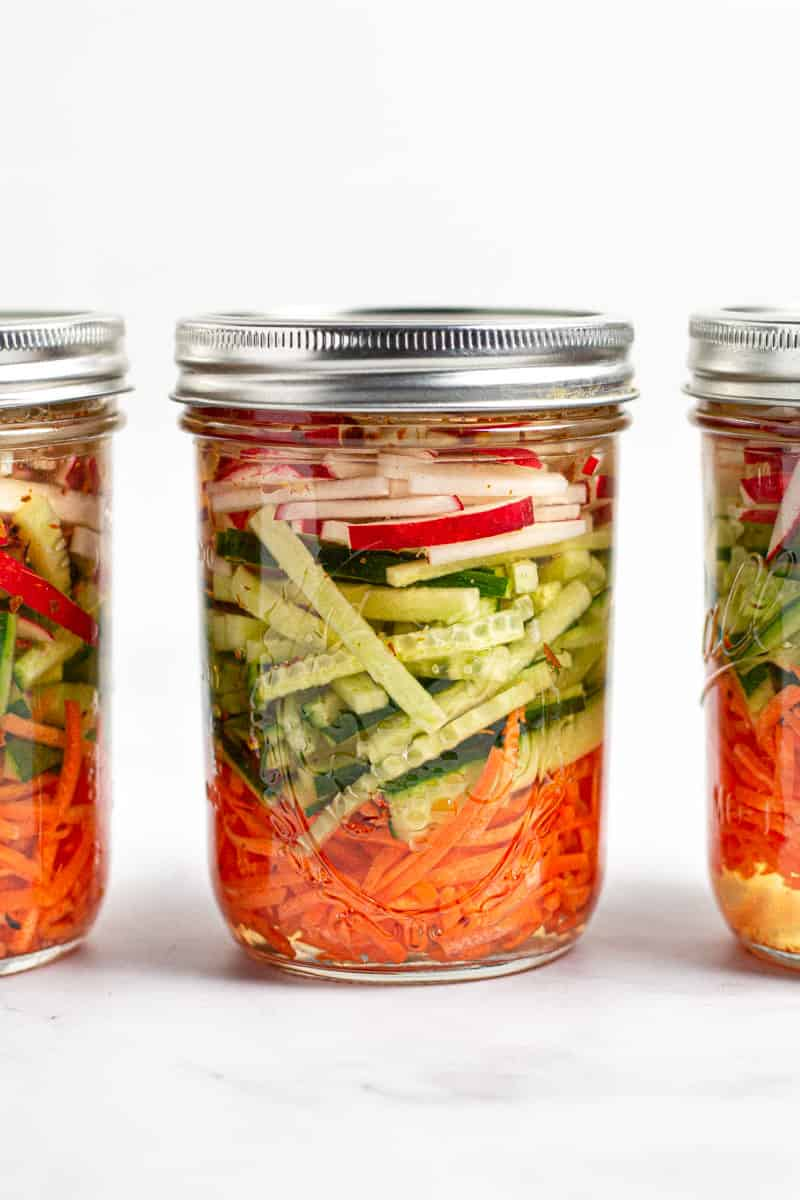 Close up shot of three jars of pickled veggies in a row