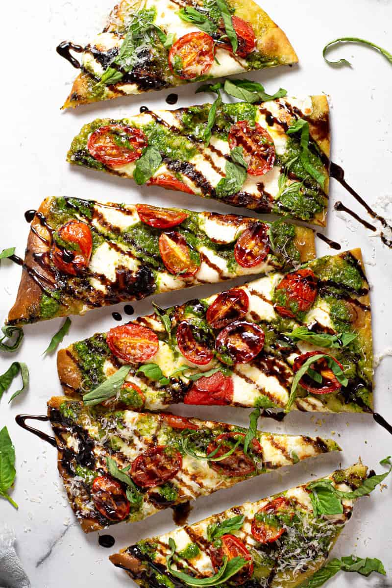 Overhead shot of a Caprese flatbread pizza drizzled with balsamic glaze