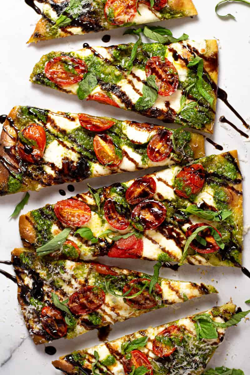 Overhead shot of a Caprese flatbread pizza drizzled with homemade spinach pesto