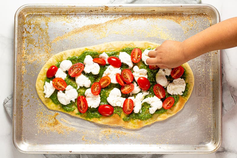 Overhead shot of a little hand placing cheese onto a Caprese flatbread on a baking sheet