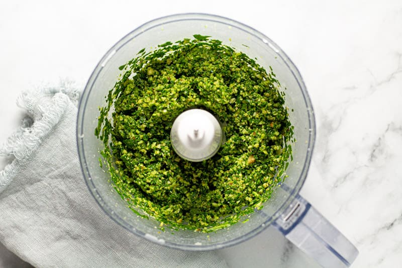 Overhead shot of a food processor with ingredients to make homemade spinach pesto