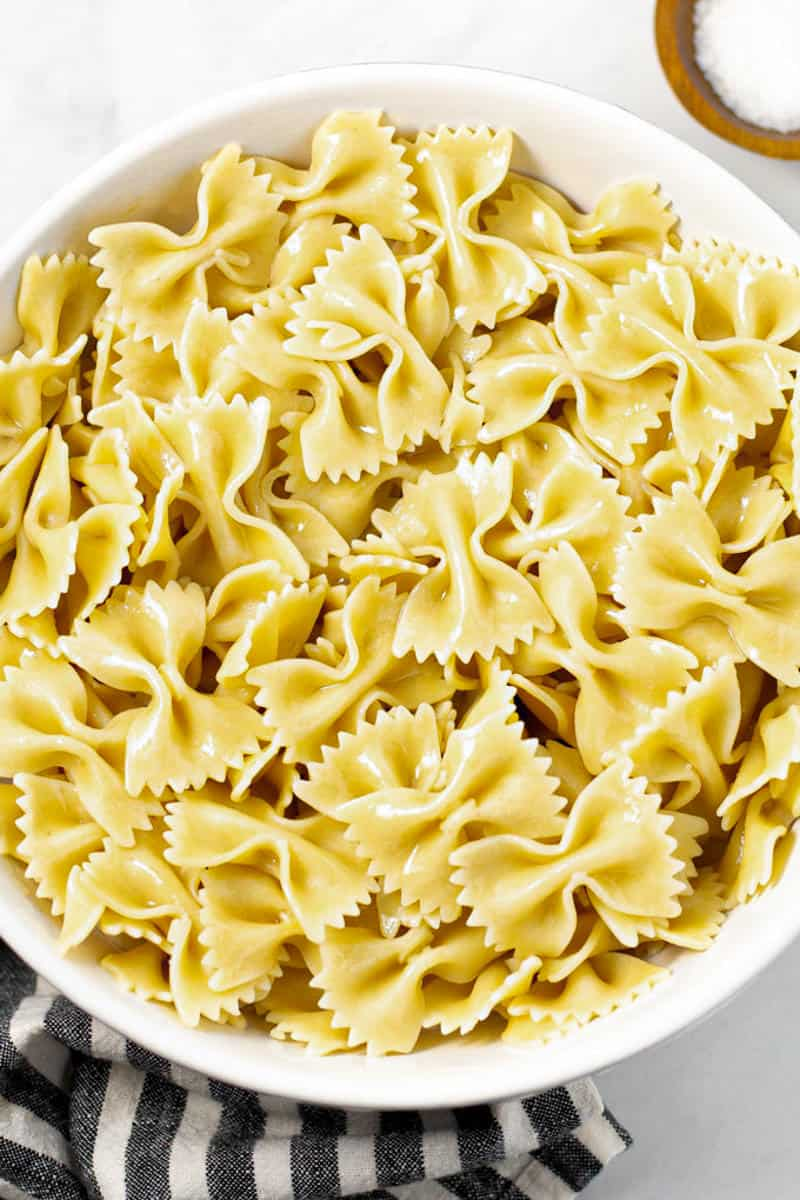 Large white bowl filled with cooked bowtie pasta