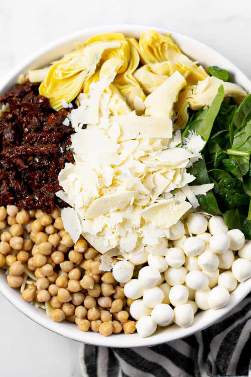 Large white bowl filled with ingredients to make pasta salad