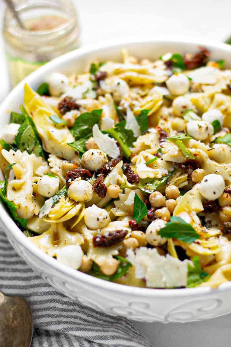 Close up shot of a bowl of sun dried tomato pasta salad garnished with fresh parsley
