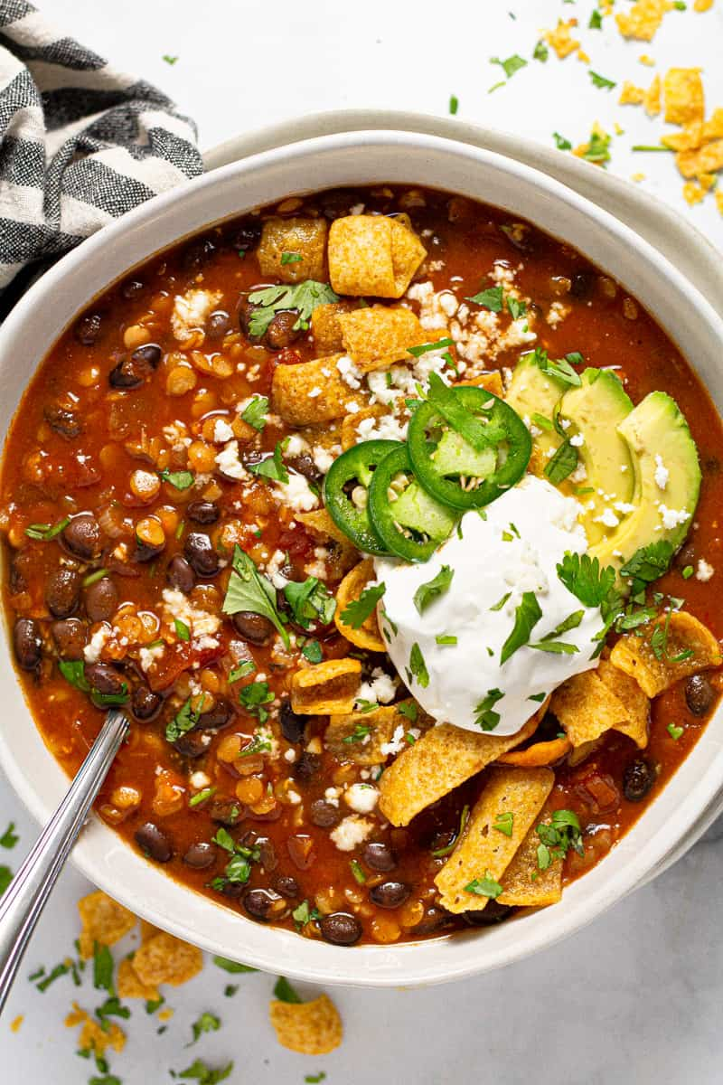 Overhead shot of a bowl of vegan black bean chili garnished with Fritos and sour cream