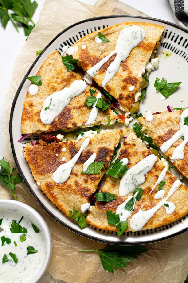 Overhead shot of a Greek quesadilla drizzled with dill yogurt sauce