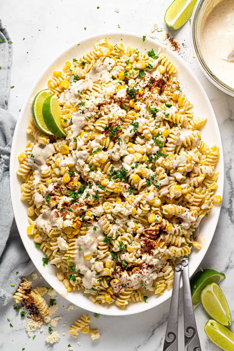 Overhead shot of a white platter filled with Mexican street corn pasta salad garnished with fresh cilantro