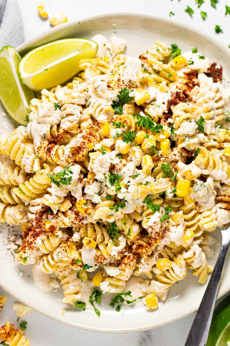 Overhead shot of a white plate filled with Mexican street corn pasta salad garnished with fresh cilantro