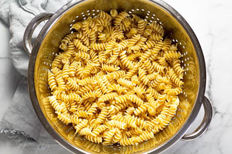Metal strainer filled with al dente rotini noodles